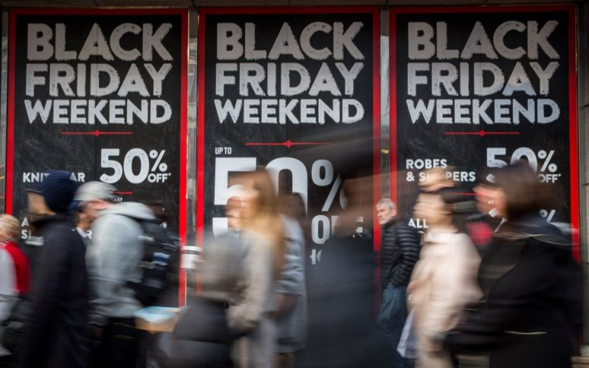 People walking by Black Friday signs
